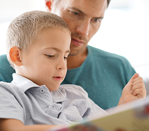 Father and young son read a book