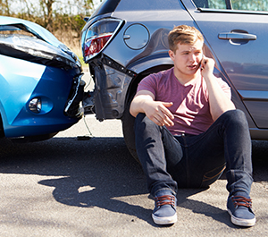 Young man makes phone call after car accident